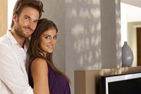 Portrait of beautiful young loving couple embracing at home in living room.