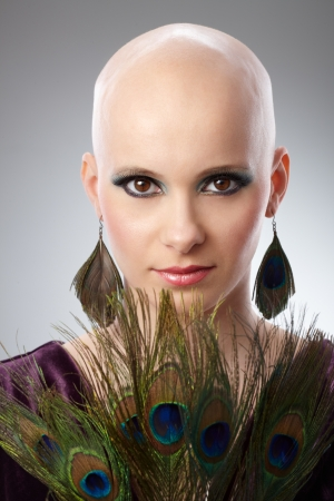 Portrait of beautiful hairless woman using peacock plumes as accessory   65533;