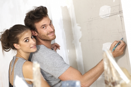 Loving couple drawing floor plan on wall, embracing, smiling happy.