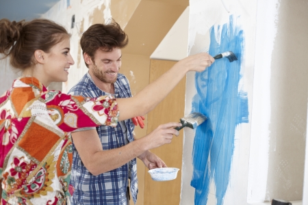 Happy young couple renewing home, painting wall to blue, smiling happy   65533;