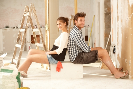 Happy young couple sitting happy in home under construction   65533;