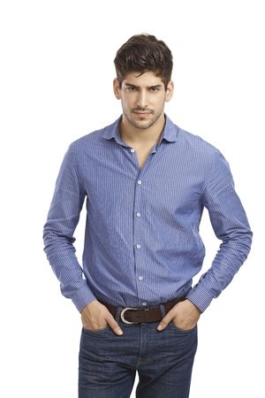 Confident young man standing in jeans and shirt with hands in pocket. Looking at camera.