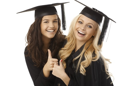 Beautiful young female graduates in square academic cap showing ok sign, hugging, smiling happy.