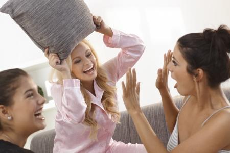 Happy girls pillow fighting in pyjamas, having fun.