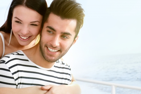 Happy young couple smiling, embracing on sailboat
