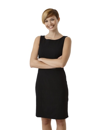 Portrait of young woman in black dress with arms crossed, isolated on white background