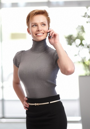 Pretty young businesswoman talking on mobilephone at office building.