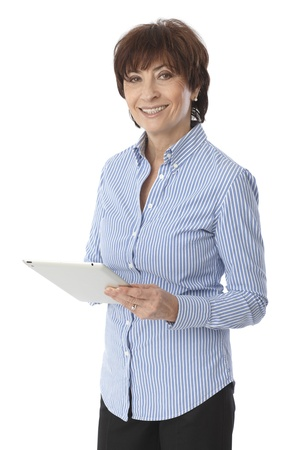 Happy senior woman standing, holding tablet computer, looking at camera.
