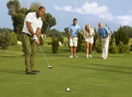 Photo pour Male golfer putting in golf ball on the green, partners jittering. - image libre de droit