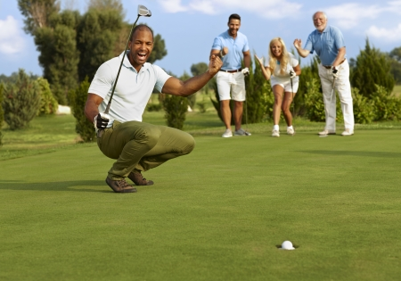 Photo pour Male golfer and partners happy for successful putt on the green. - image libre de droit