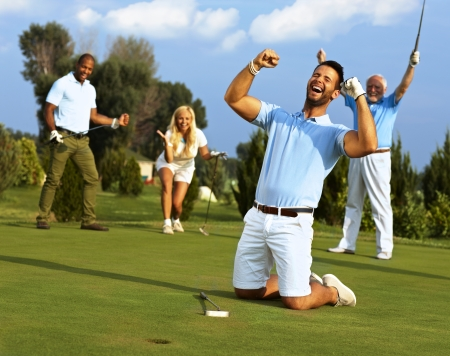 Photo pour Happy golfer kneeling at hole with raised fists after putting in golf ball to the hole. - image libre de droit