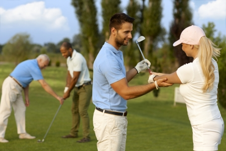Photo pour Female golfer learning golfing, male instructor helping. - image libre de droit
