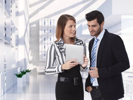 Formal clothed business partners holding tablet discussing at office, smiling.