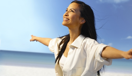 Beautiful Asian girl smiling happy on the beach, pretending to fly with arms wide open, enjoying freedom and sun.