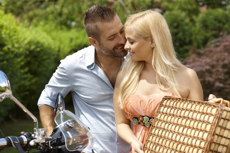 Happy casual caucasian couple with scooter and picnic basket. Blonde smiling woman with handsome man, outdoor.