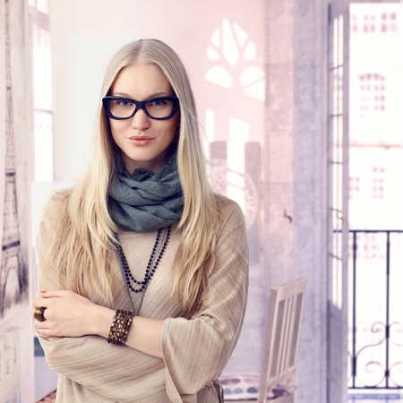 Young trendy casual caucasian blonde woman with glasses at retro home. Standing, arms crossed, smiling looking at camera. Wearing jewelry, copyspace.