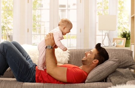 Photo pour Happy father lying on sofa holding baby girl, playing, smiling. Side view. - image libre de droit
