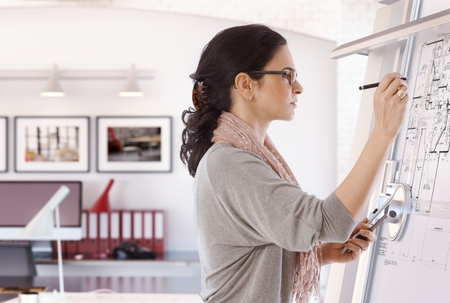 Focused casual caucasian female architect working at drawing board with pen in hand. Wearing glasses, at office. Floor plan, busy, concentration, unsmiling.