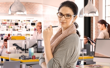 Foto de Casual caucasian businesswoman at business startup office with pen in hand, wearing glasses. Looking at camera, scarf around neck. - Imagen libre de derechos