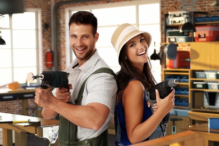 Photo pour Happy young caucasian casual couple having fun at home workshop. Smiling, looking at camera, holding power drill in hand, standing. Handsome man, attractive female. Do it yourself. - image libre de droit