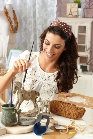 Young woman enjoying hobby painting in vintage style at old-fashioned home, smiling.