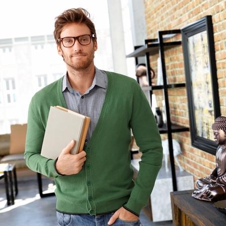 Photo pour Portrait of young man holding books, looking at camera. - image libre de droit