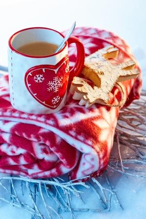 Winter decoration with mug of tea, reindeer and blanket.