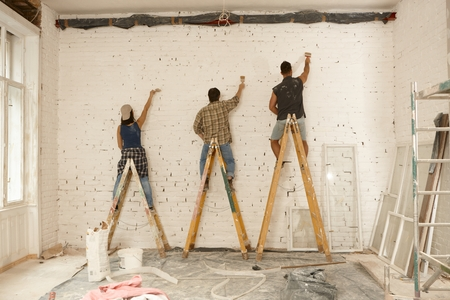 Photo for Painter team working on renovation site, standing on ladder, painting wall by brush. - Royalty Free Image