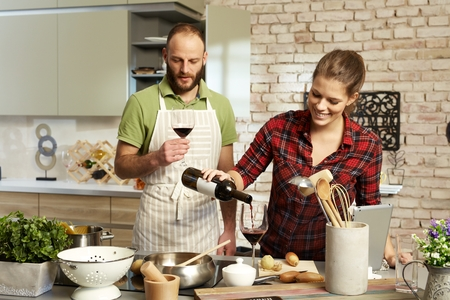 Photo pour Happy couple cooking together in kitchen, drinking red wine. - image libre de droit
