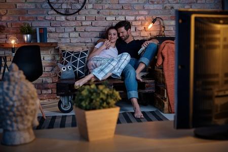 Photo pour Young loving couple watching tv at home, embracing. - image libre de droit