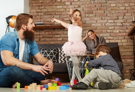 Family with two children playing together at home.