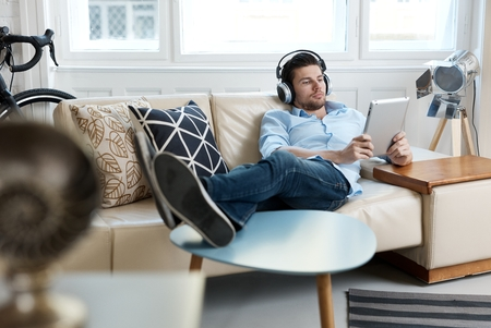 Photo pour Young man lying on sofa, using tablet and headphones. - image libre de droit