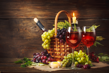 Foto de Basket with fresh grapes and a glass of wine on a wooden table. Autumn background. - Imagen libre de derechos