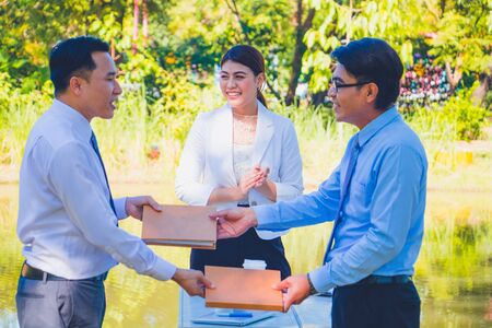Photo pour Business man handing a contract agreement and after a deal between business success.Business women clapping nice and smile.They are happy beside stream in park.Photo concept business and succeed. - image libre de droit