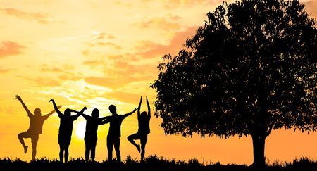 Photo pour Silhouetted photo.They are standing with big tree and show hand together.They are enjoying and also they are watching the evening glow together. They are happy in good time.  Photo concept for Silhoue - image libre de droit