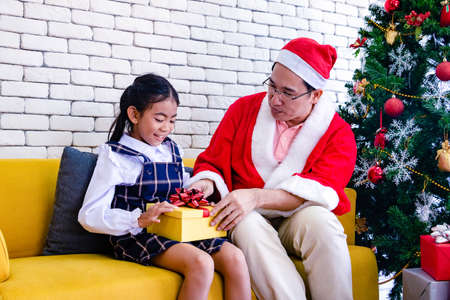 Young Asia Santa Claus with gift. He is sent gift box in Merry Christmas day , Sent happy , Photo new year and Merry Christmas concept idea.