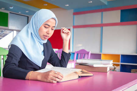 Photo pour Young student Islamic woman. She is sitting and reading book.She is smile and relax time, woman Portrait, Photo concept portrait and life style. - image libre de droit