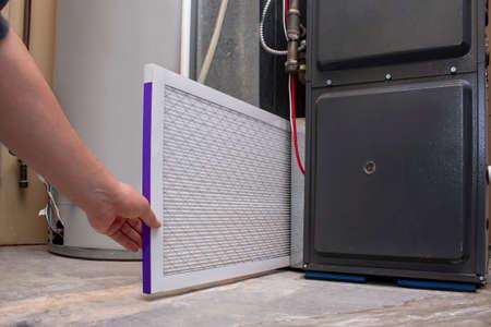 Photo pour A person changing an clean air filter on a high efficiency furnace - image libre de droit