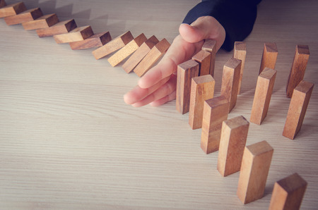 Foto de Businesswoman hand stopping the domino wooden effect concept for business. Risk. - Imagen libre de derechos