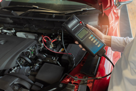 Photo pour Man inspection holding Battery Capacity Tester Voltmeter.for service  maintenance of industrial to engine repair.In Factory transport automobile automotive image - image libre de droit