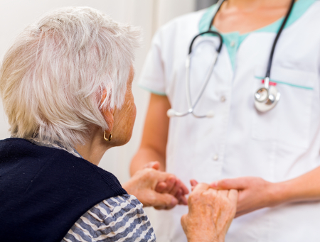 Photo pour Young doctor giving helping hands for elderly woman - image libre de droit