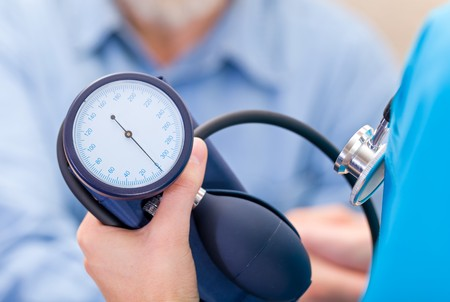 Photo of young doctor measures the blood pressure