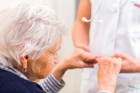 Foto de Young doctor giving helping hands for elderly woman - Imagen libre de derechos