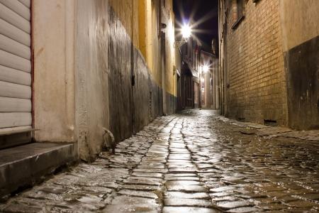 Old wet cobblestone street after rain at night