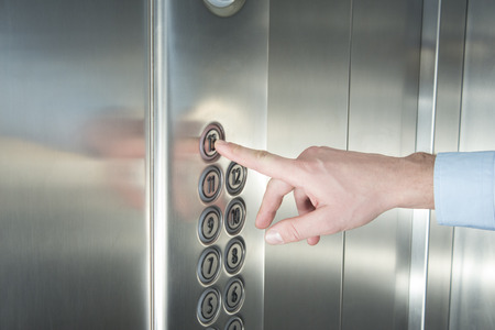 Photo pour Human hand pressing the last floor button in the elevator - image libre de droit