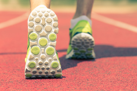 Photo for Back side view close up shot of feet with running shoes on the red running track. Jogging, training, fitness and healthy lifestyle concepts. - Royalty Free Image