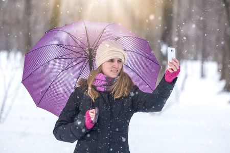 Woman with umbrella taking selfie with smartphone and enjoying winter season in park.