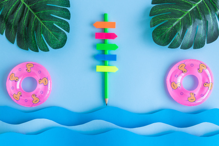 Photo pour Direction sign made of pencil and colorful sticky notes with waves, monstera leaves and pool floats minimal creative summer travel vacation concept. - image libre de droit