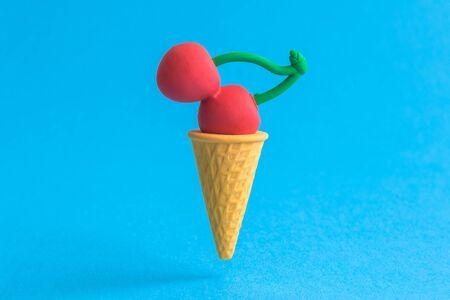 Foto de Ice cream cone with cherry against pastel blue background minimal summer sweet food creative concept. - Imagen libre de derechos