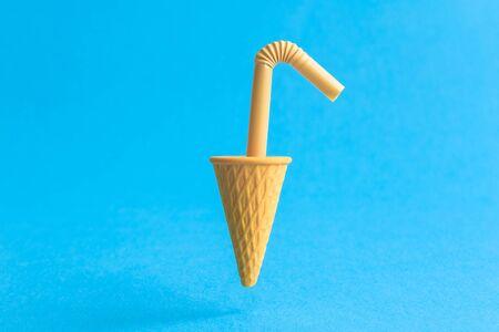 Foto de Ice cream cone with drinking straw against pastel blue background minimal summer food and drink creative concept. - Imagen libre de derechos